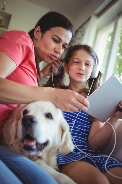 Mãe e filha sentada com cachorro de estimação e usando digital Foto Premium