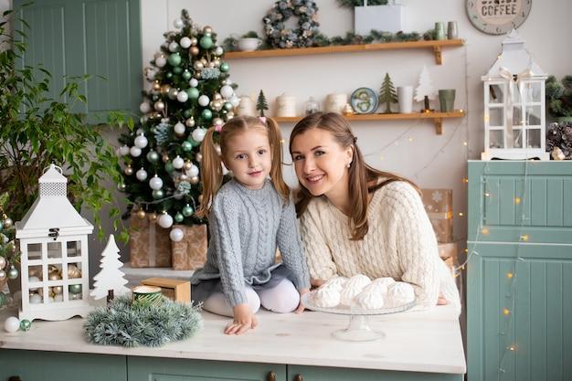 Mãe e filha sorrindo na cozinha de natal em casa. Foto Premium