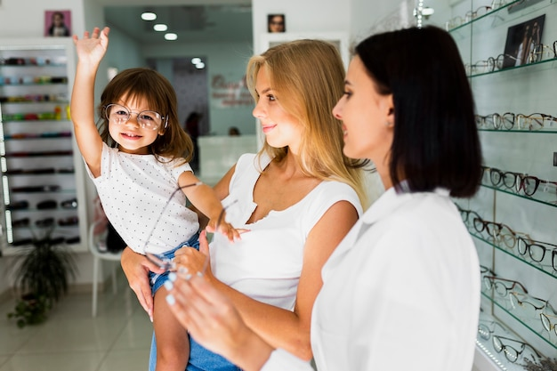 Mãe e filha tentando armações de óculos Foto gratuita