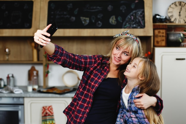 Mãe e filha tirar uma selfie de pé em uma cozinha aconchegante nas mesmas camisetas Foto gratuita