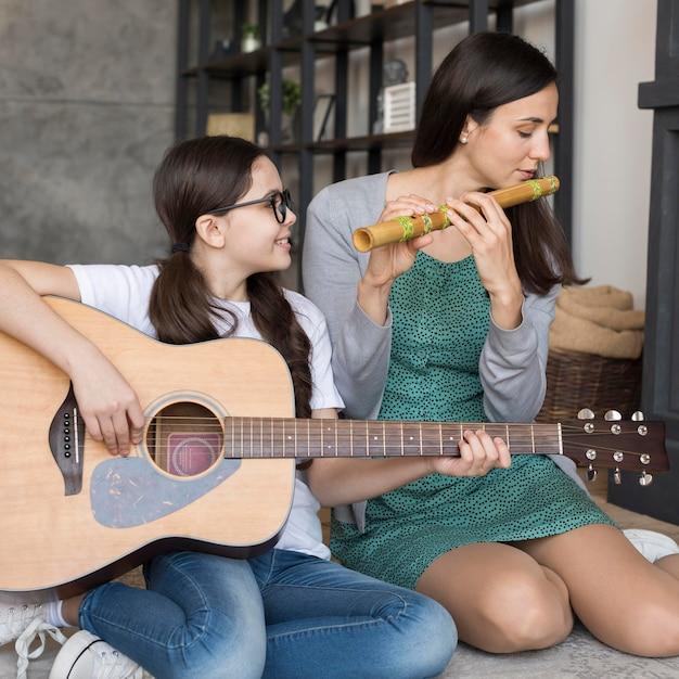 Mãe e filha tocando instrumento Foto gratuita