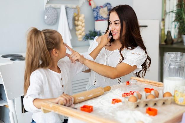Mãe e filha tocando um ao outro nariz Foto gratuita
