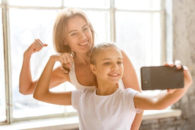 Mãe e filha tomando selfie flexionando os músculos do braço Foto gratuita