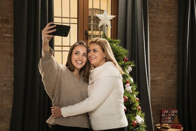 Mãe e filha tomando uma selfie juntos Foto gratuita