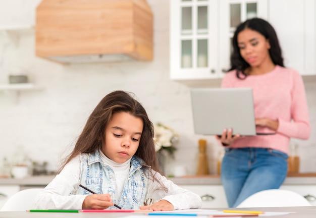Mãe e filha trabalhando Foto gratuita