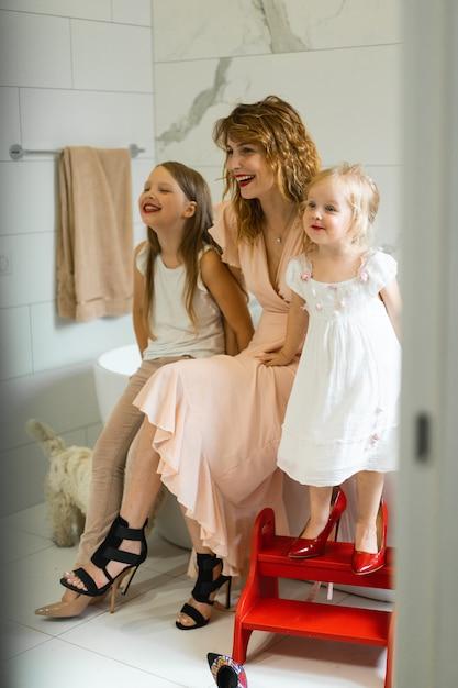Mãe e filhas fazem maquiagem no banheiro, aplique batom na frente do espelho. Foto gratuita