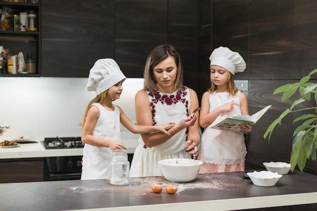 Mãe e filhas preparando comida na cozinha Foto gratuita