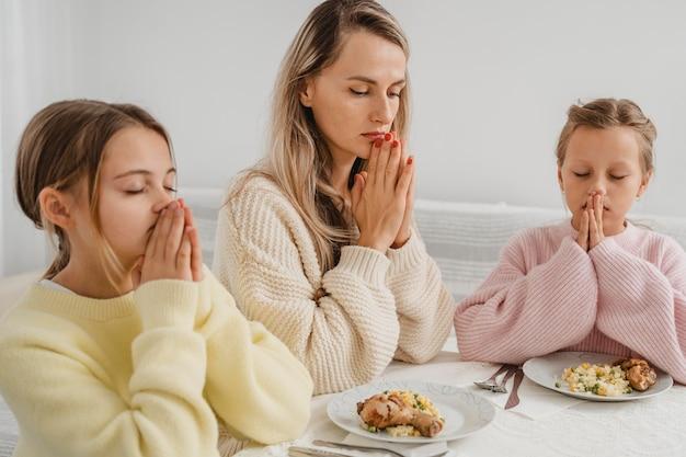 Mãe e filhas rezando à mesa de jantar Foto Premium