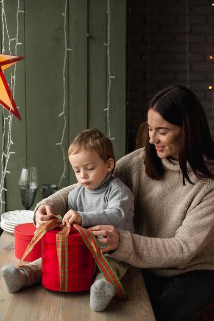 Mãe e filho abrindo presente de natal Foto gratuita