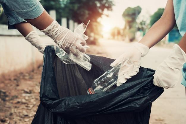 Mãe e filho ajudam a recolher o lixo no parque Foto Premium