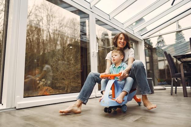 Mãe e filho andam pelo apartamento em um carro de brinquedo Foto gratuita