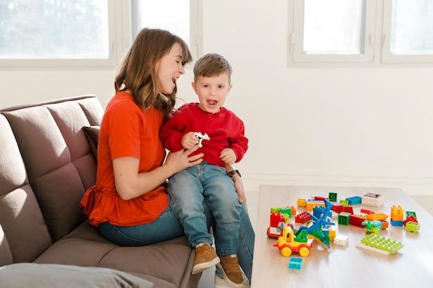 Mãe e filho brincando com brinquedos Foto gratuita