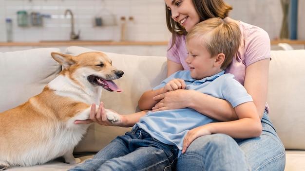 Mãe e filho brincando com cachorro corgi Foto gratuita