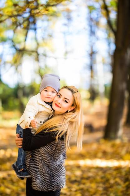 Mãe e filho caminhando em um parque de outono Foto gratuita