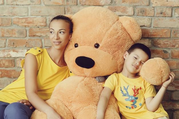 Mãe e filho com enorme urso de pelúcia Foto gratuita