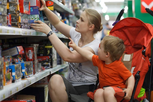 Mãe e filho, compras de brinquedos Foto Premium