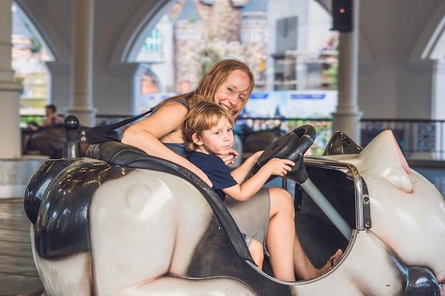 Mãe e filho dando uma volta no carro de choque no parque de diversões. Foto Premium