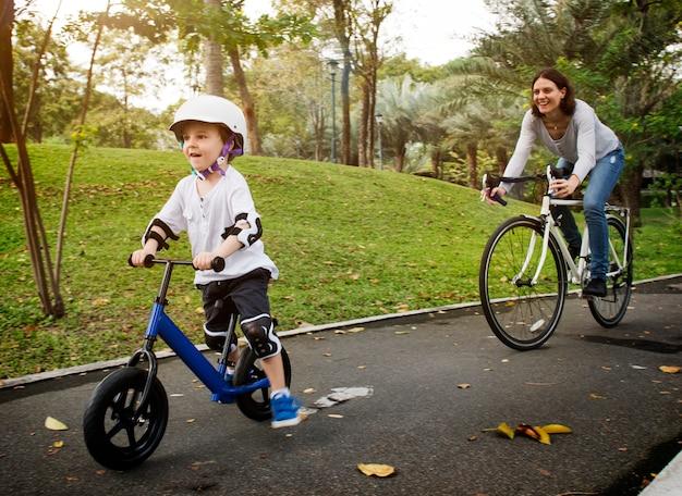 Mãe e filho de bicicleta no parque Foto Premium