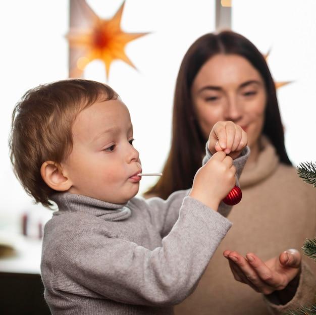Mãe e filho decorando a árvore de natal Foto gratuita