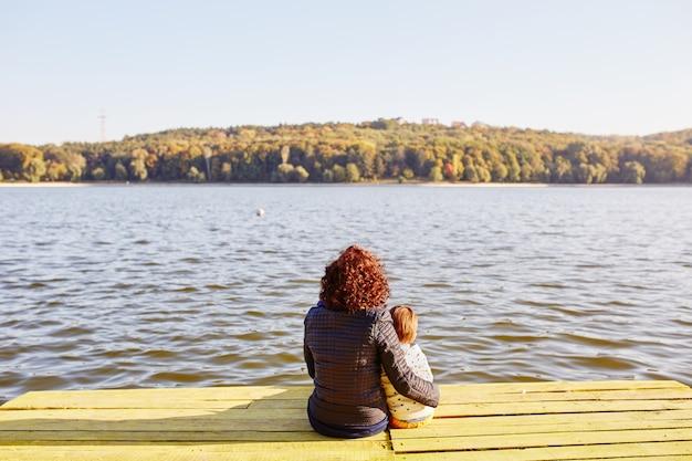 Mãe e filho descansando à beira do lago Foto gratuita