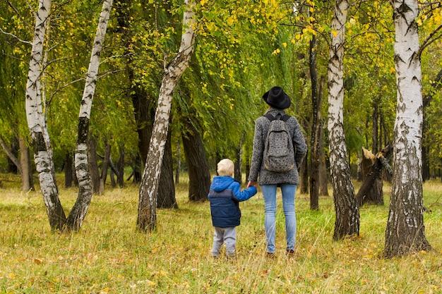Mãe e filho estão andando na floresta de outono Foto Premium