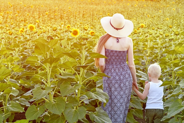 Mãe e filho estão andando no campo de girassóis em flor. vista traseira Foto Premium