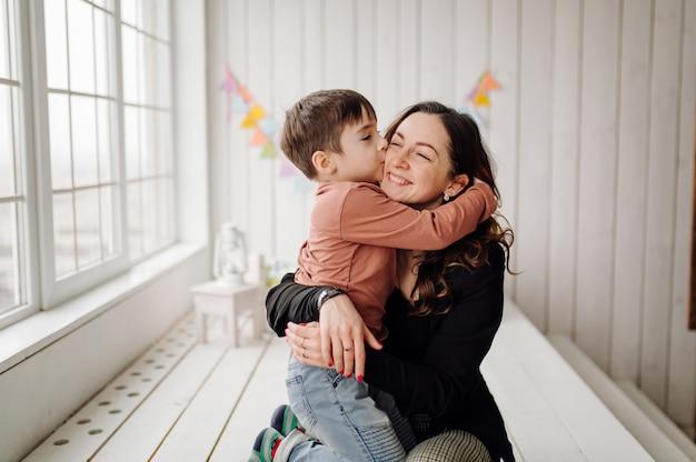 Mãe e filho estão posando no estúdio e vestindo roupas casuais Foto gratuita