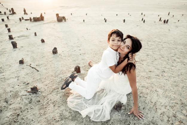 Mãe e filho estão sentados na areia, vestidos com roupas brancas, sorrindo e abraçando Foto gratuita