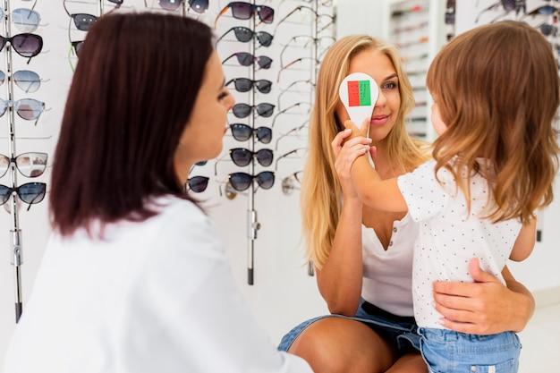 Mãe e filho no exame oftalmológico Foto gratuita