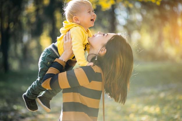 Mãe e filho no parque de outono Foto gratuita