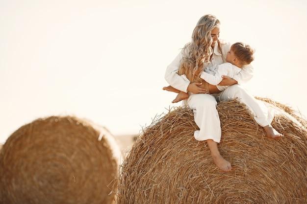 Mãe e filho. pilha de feno ou fardo no campo de trigo amarelo no verão. crianças se divertindo juntos. Foto gratuita