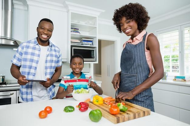 Mãe e filho preparando salada enquanto pai usando tablet digital na cozinha em casa Foto Premium
