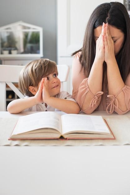 Mãe e filho rezando juntos Foto gratuita