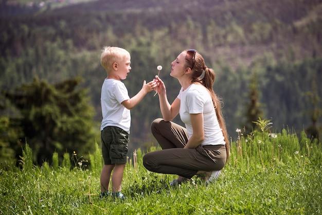 Mãe e filho soprar dente de leão. maternidade e amizade Foto Premium