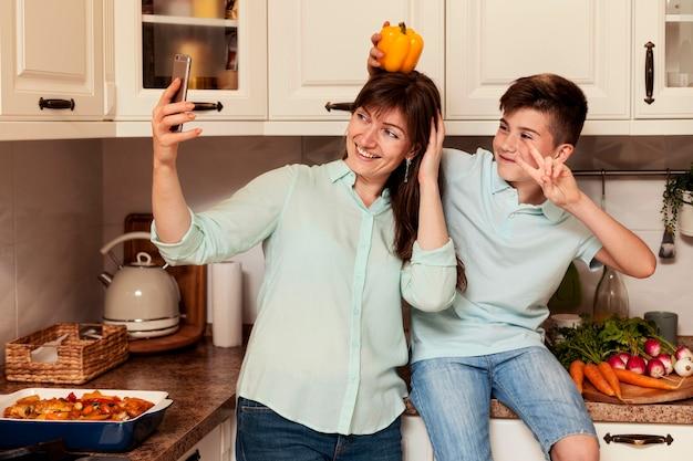 Mãe e filho tomando selfie na cozinha com legumes Foto gratuita