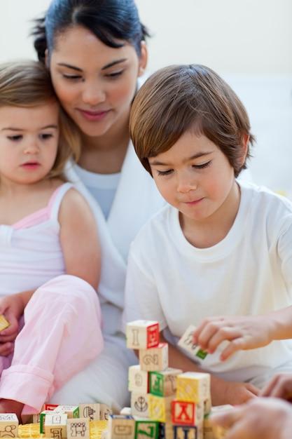 Mãe e filhos brincando com blocos alfabéticos Foto Premium