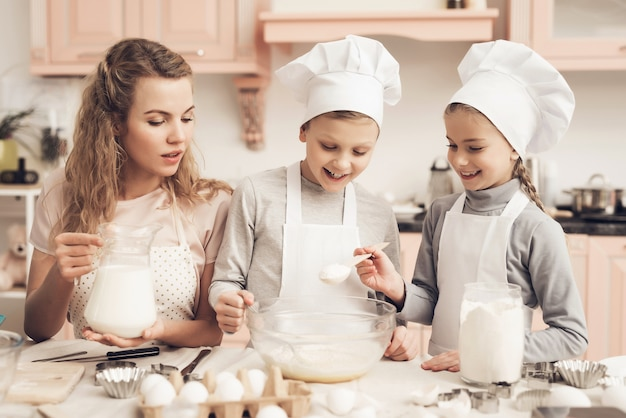 Mãe e filhos fazendo uma massa garota feliz adiciona o açúcar. Foto Premium