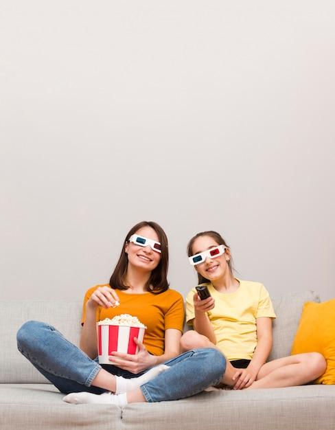Mãe e menina assistindo filmes Foto gratuita
