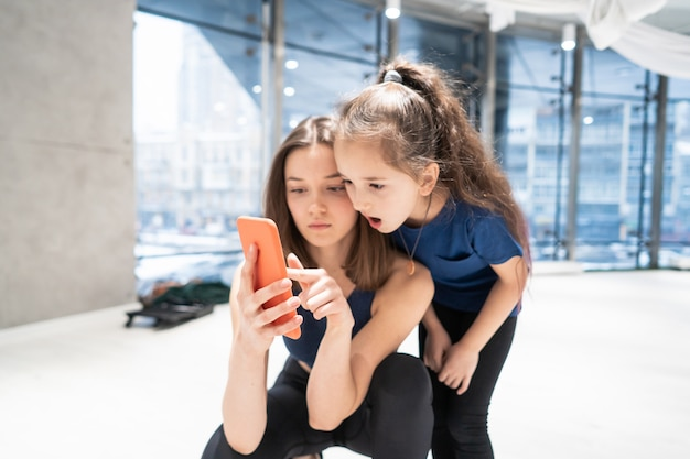 Mãe e menina usando telefone no ginásio para assistir vídeo Foto gratuita