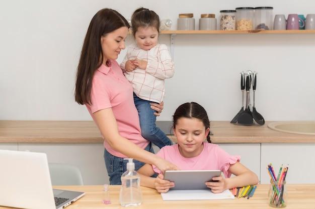 Mãe e meninas com dispositivos Foto gratuita