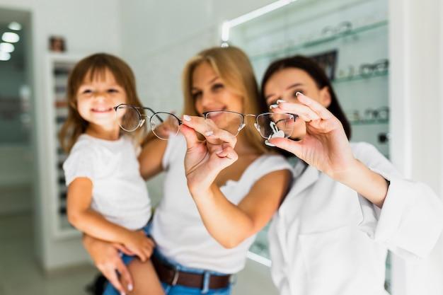Mãe e oculista segurando armações de óculos Foto gratuita