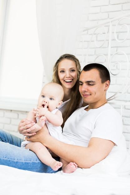 Mãe e pai com bebê em uma cama Foto Premium