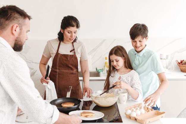Mãe e pai com dois filhos de 8 a 10 cozinhando juntos e fritando panquecas no fogão moderno na cozinha de casa Foto Premium