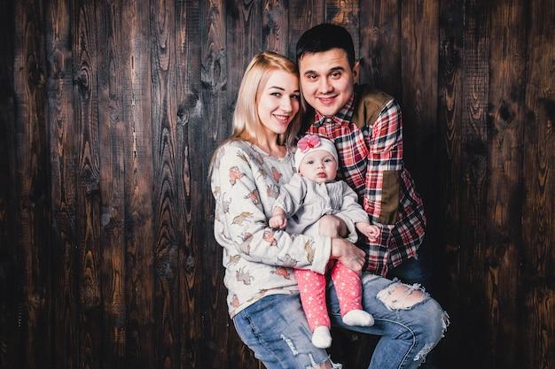 Mãe e pai com seu bebê em uma cadeira de bar no contexto de uma parede de madeira Foto Premium