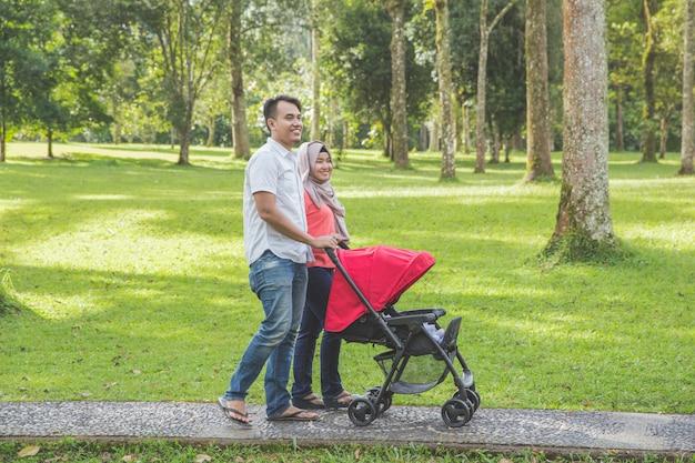 Mãe e pai empurrando carrinho de bebê no parque Foto Premium