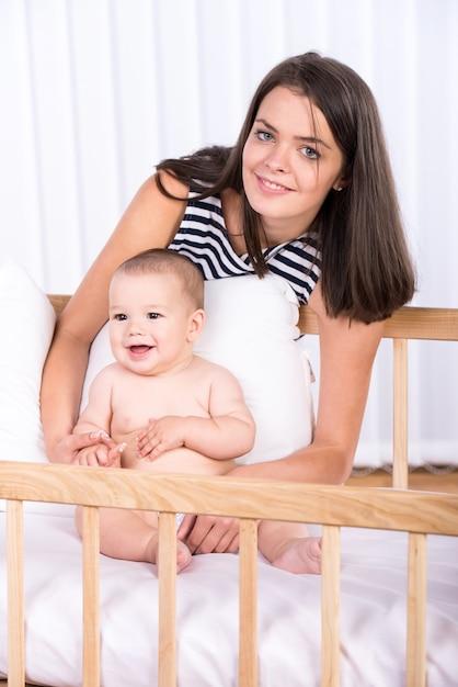 Mãe e seu bebezinho no berço em casa. Foto Premium