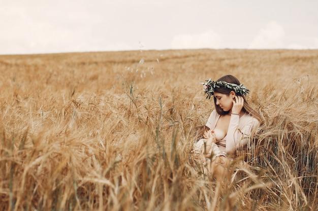 Mãe elegante com filha pequena em um campo Foto gratuita