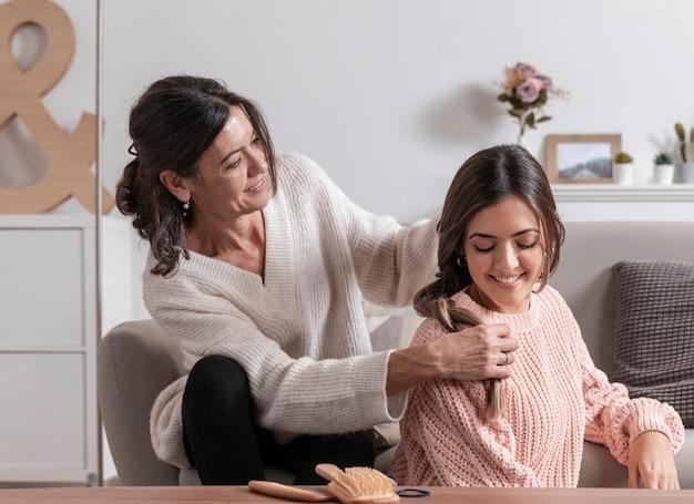 Mãe em casa trança cabelo de menina Foto gratuita