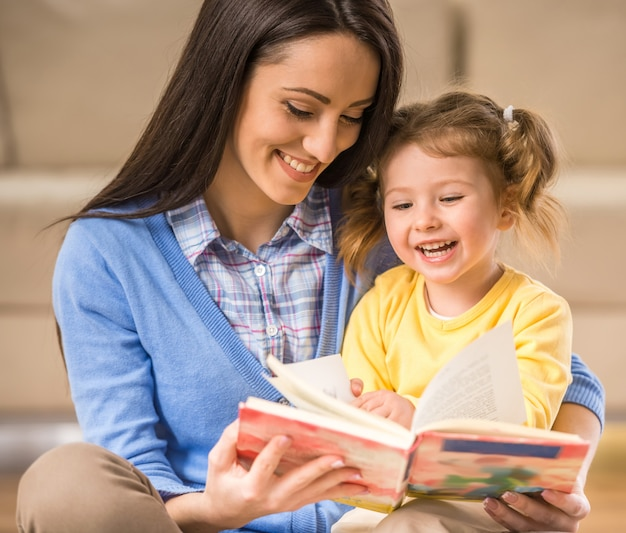 Mãe encantadora está mostrando imagens em um livro. Foto Premium