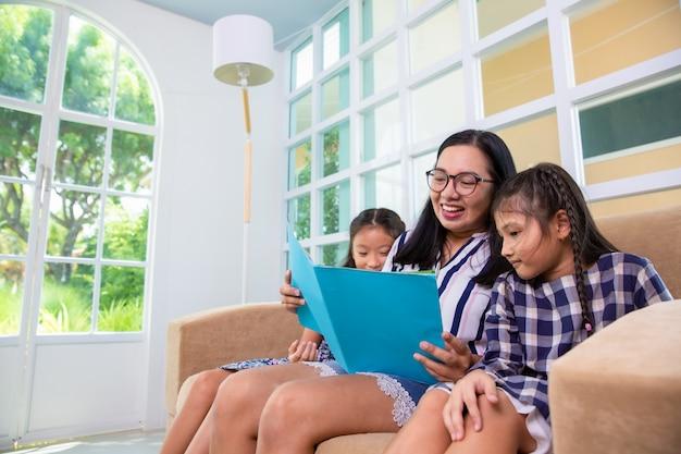 Mãe, ensinando, daughteres, livro leitura, ligado, sofá, casa Foto Premium